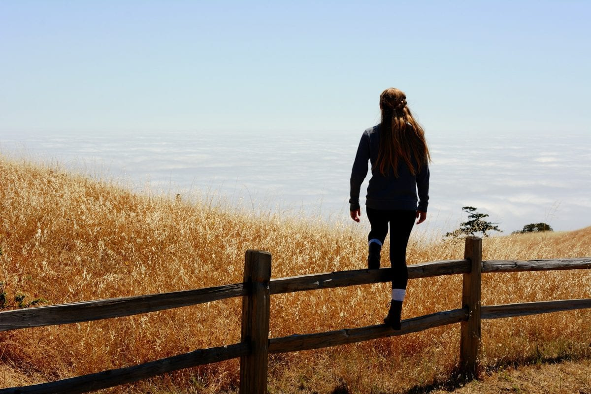 Girl standing on wooden fence.